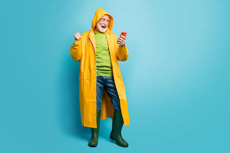 Full length body size view of his he nice cheerful satisfied grey-haired man wearing long yellow topcoat using cell having fun free time isolated on bright vivid shine vibrant blue color background