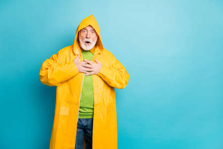 Portrait of his he nice attractive frightened amazed grey-haired man wearing yellow coat cyclone news reaction heart attack isolated on bright vivid shine vibrant blue color background