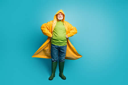 Full length body size view of his he serious content grey-haired man wearing long yellow topcoat north cyclone climate change rainy day isolated on bright vivid shine vibrant blue color background