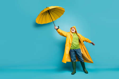 Full length body size view of his he cheerful cheery dreamy grey-haired man wearing, yellow topcoat bad cold weather cyclone day isolated over bright vivid shine vibrant blue color background