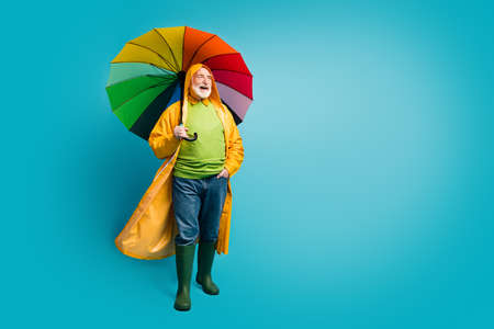 Full length body size view of his he nice cheerful grey-haired man wearing, yellow plastic topcoat parasol strolling spending rainy day isolated over bright vivid shine vibrant blue color background Stock Photo