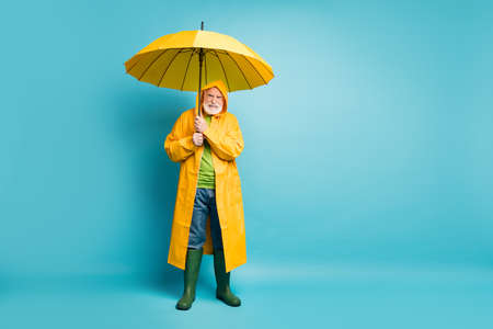 Full length body size view of his he dissatisfied mad irritated grey-haired man fisherman, wearing yellow topcoat bad weather day isolated over bright vivid shine vibrant blue color background