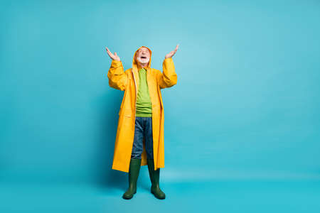 Full length body size view of his he nice cheerful cheery positive glad grey-haired man wearing, yellow topcoat expecting rain drop isolated over bright vivid shine vibrant blue color background