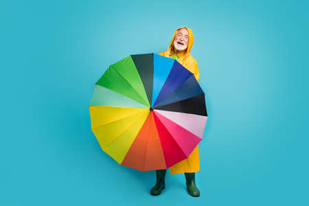 Full length body size view of his he nice cheerful cheery friendly grey-haired man wearing yellow topcoat spinning colorful parasol isolated over bright vivid shine vibrant blue color background Stock Photo