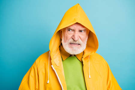 Close-up portrait of his he dissatisfied evil irritated annoyed grey-haired man wearing yellow overcoat bad rainy weather isolated over bright vivid shine vibrant blue color background