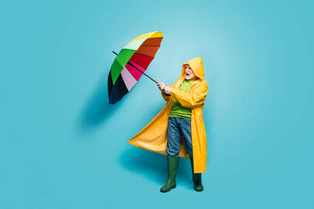 Full length body size view of his he nice irritated grey-haired man wearing yellow topcoat struggling wind bad weather isolated over bright vivid shine vibrant blue color background