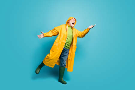Full length body size view of his he nice cheerful positive grey-haired man wearing yellow topcoat catching rainy drop having fun isolated over bright vivid shine vibrant blue color background