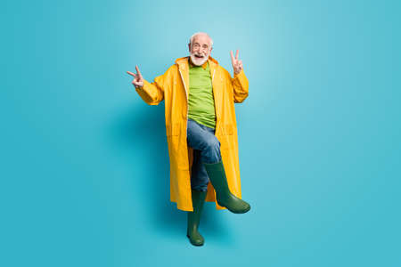 Full length body size view of his he nice cheerful cheery grey-haired man wearing topcoat dancing showing double v-sign good mood isolated over bright vivid shine vibrant blue color background Stock Photo