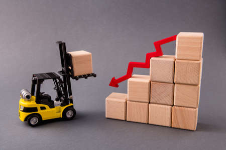 Photo of electric loader bringing wooden cubes supply management, building commerce reducing profit arrow pointing down isolated over dark pastel grey color background Archivio Fotografico