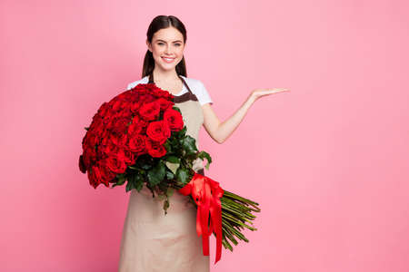 Photo of attractive friendly floral shop assistant lady cheerful mood hold one hundred roses bunch low price open arm wear apron t-shirt isolated pastel pink color background