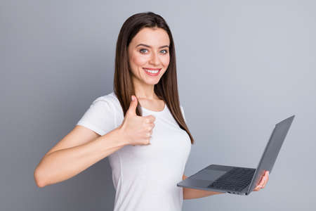 Portrait of confident positive girl manager entrepreneur enjoy corona virus quarantine working home show thumb up sign hold laptop wear white t-shirt isolated over gray color background