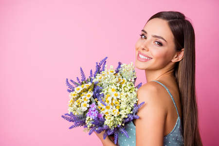 Close-up profile side view portrait of nice-looking attractive lovely pretty winsome charming cute cheerful cheery girl holding in hands flowers isolated over pink pastel color background