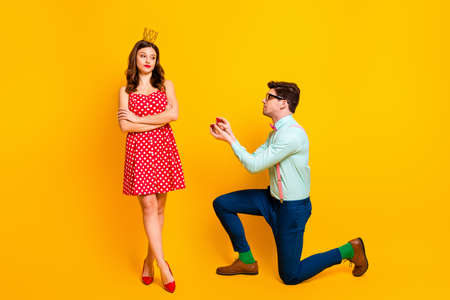 Full body photo of pretty boast lady handsome guy proposing girlfriend stand knee hold diamond ring box selfish queen not sure with answer wear retro clothes isolated yellow color background