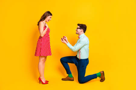 Full body profile photo of pretty lady handsome guy couple proposing girlfriend stand one knee hold diamond ring box wear red dress shirt bowtie isolated yellow bright color background