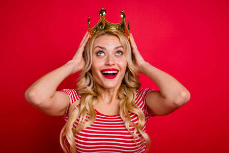 I am prom queen wow omg unbelievable. Astonished positive cheerful girl put gold tiara head she get graduation event victory wear trendy outfit isolated over shine color background Foto de archivo