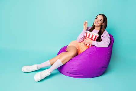 Full length profile photo of cheerful lady sit bean bag chair eat popcorn watch favorite show good mood wear purple sweater orange mini skirt shoes socks isolated teal color background Banque d'images