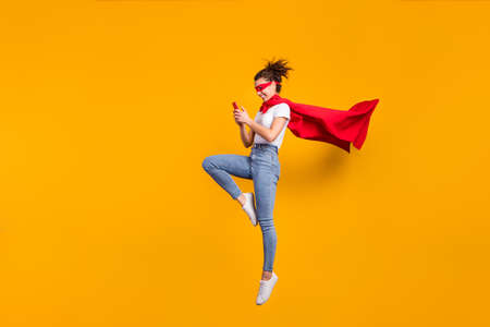 Full length body size view of her she nice attractive lovely cheerful focused girl jumping wearing cape using digital device 5g app isolated on bright vivid shine vibrant yellow color background