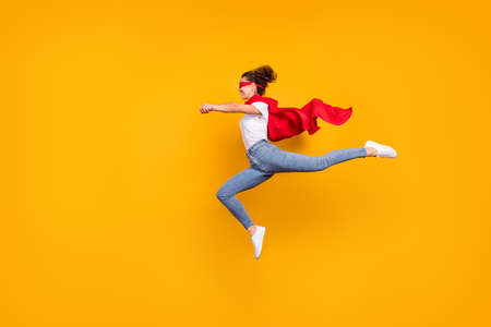 Full length body size view of her she nice attractive lovely fit slim cheerful energetic girl jumping wearing cape running rescuing planet isolated bright vivid shine vibrant yellow color background
