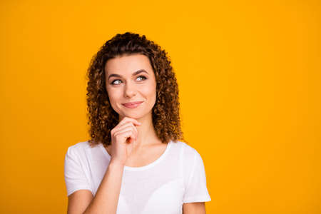Photo of attractive cute lady arm on chin thinking perfect pretty curls hairdo look up side empty space interested wear casual white t-shirt isolated yellow vibrant color background
