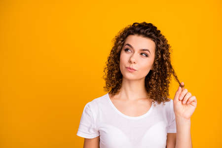 Photo of attractive pretty cunning lady wound perfect pretty curl hairdo on finger look side empty space interested wear casual white t-shirt isolated yellow vibrant color background