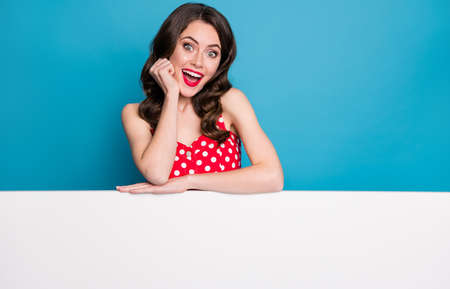Photo of attractive impressed lady lean hands empty advert banner sales manager read information shopping wear summer red white dotted retro dress isolated blue color background Zdjęcie Seryjne