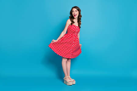 Full length photo of pretty lady mischief good mood flirty raise skirt hands look side empty space wear summer red white dotted retro dress open toes shoes isolated blue color background Foto de archivo