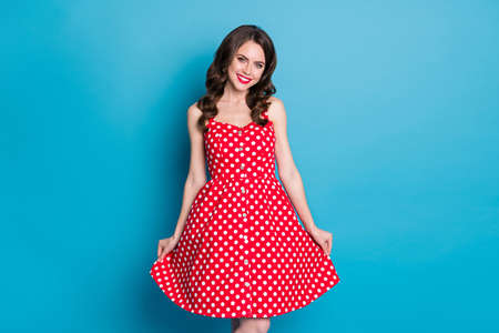 Photo of stunning attractive pretty curly lady bright shiny pomade smiling white teeth good mood flirty hold skirt wear red white dotted retro dress isolated blue color background