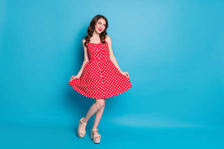 Full length photo of attractive lady shiny pomade smiling toothy flirty hold skirt shy look empty space wear red white dotted retro dress summer open toe shoes isolated blue color background Foto de archivo
