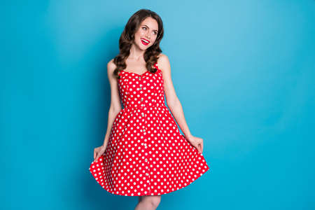 Photo of stunning attractive curly lady bright pomade smiling white teeth good mood flirty hold skirt shy look empty space wear red white dotted retro dress isolated blue color background