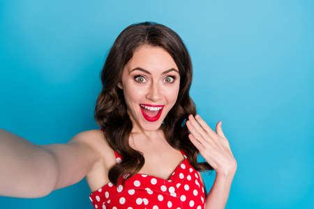 Closeup photo of attractive pretty curly lady smiling good mood making selfies popular blogger open mouth excited wear red dotted retro dress singlet isolated blue color background