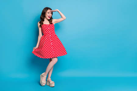 Full size photo of attractive lady shiny pomade smiling hold skirt playful mood look far away traveler wear red white dotted retro dress summer open toe shoes isolated blue color background