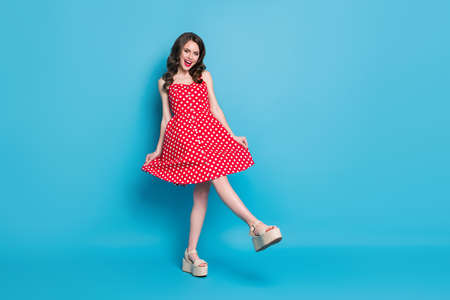 Full body photo of attractive lady shiny pomade smiling toothy flirty hold skirt playful mood raise leg wear red white dotted retro dress summer open toe shoes isolated blue color background
