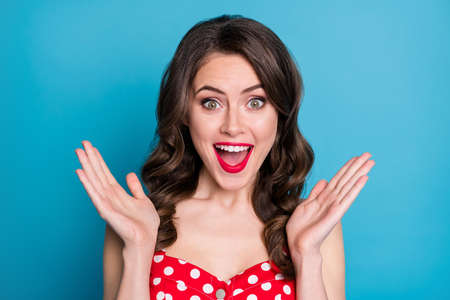 Closeup photo of pretty funny wavy lady raise arms up open mouth excited listen good news overjoyed expression wear red dotted dress singlet isolated blue color background