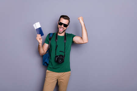 Portrait ecstatic crazy lucky guy hold tickets win summer worldwide tour raise fists scream wear backpack professional camera green t-shirt pants trousers isolated gray color background