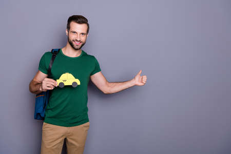 Portrait of positive guy showing finger hailing taxi cab enjoy tourism weekend wear green t-shirt pants trousers backpack isolated over gray color background