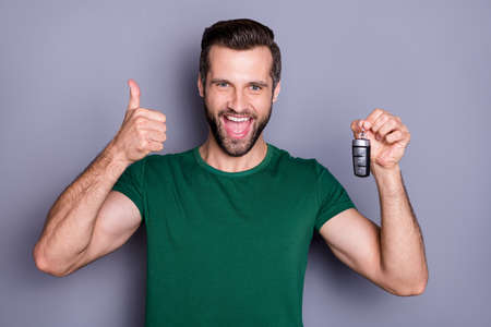Portrait of excited positive guy car buyer hold keys enjoy excellent purchase show thumb up sign wear green t-shirt isolated over gray color background