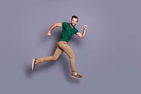 Full length profile side photo of excited guy jump run after spring season time discount wear good look clothes footwear isolated over gray color background