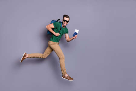 Full body profile side photo of excited energetic guy jump run celebrate lucky tour victory hold visa documents wear green t-shirts pants trousers backpack isolated gray color background
