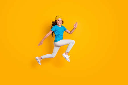 Full body profile photo of funny little lady jumping high good mood cheerful jogging competition race wear casual blue t-shirt headband trousers shoes isolated yellow color background Reklamní fotografie
