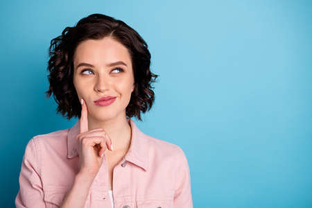 Closeup photo of attractive pretty interested lady short black hairdo look side empty space wondered arm on cheek wear casual pink denim jacket isolated blue color background