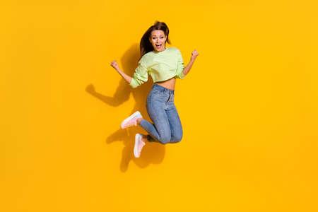 Full size photo of energetic ecstatic girl enjoy lottery discount win jump raise fists scream wear good look outfit isolated over shine color background