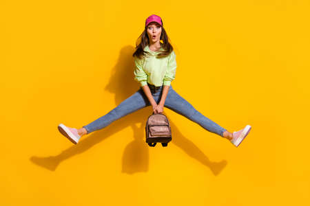 Full size photo of funky energetic attractive lady student good mood hold backpack jump high up wear green cropped sweatshirt jeans shoes cap isolated vivid bright yellow color background