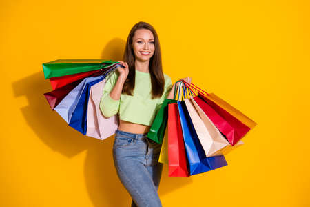 Photo of pretty charming shopaholic lady good mood street look hold many shopping bags wear green cropped sweatshirt jeans isolated vivid bright yellow color background