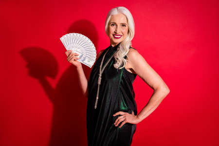 Photo of attractive beautiful aged grey haired lady good mood hold fan money bucks come to casino ready to play luxury look makeup wear shine glossy dress isolated red color background 스톡 콘텐츠