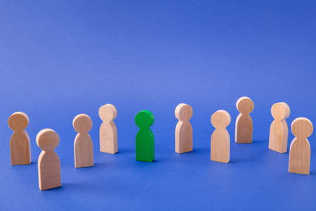 Crowd of wooden faceless people figures different social layers walking. One special eco-friendly guy alone in big city isolated over bright vivid shine vibrant blue color background