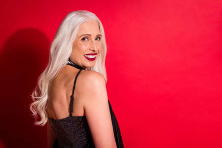 Profile photo of attractive aged grey haired lady luxury look evening makeup posing camera toothy smile photographing wear shine glossy fashion dress isolated red color background Archivio Fotografico