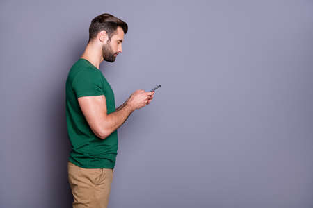 Profile side photo of focused guy have summer walk use smartphone comment subscribe post read social network corona virus information wear good look clothes isolated gray color background