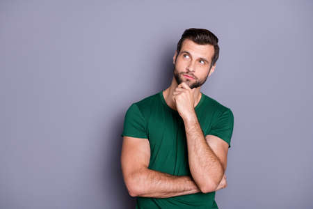 Photo of attractive handsome bearded guy hold arm in chin look up empty space wondered intelligent creative person wear casual green t-shirt isolated grey color background