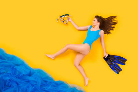 Full length high angle above flat lay view profile photo of beautiful lady seaside resort run into water mask flippers professional diver wear bodysuit isolated yellow color background 免版税图像