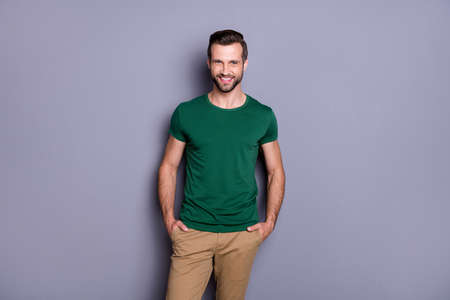 Photo of attractive guy business man perfect neat hairdo bristle appearance smiling beaming good mood hands pockets wear casual green t-shirt pants isolated grey color background Zdjęcie Seryjne